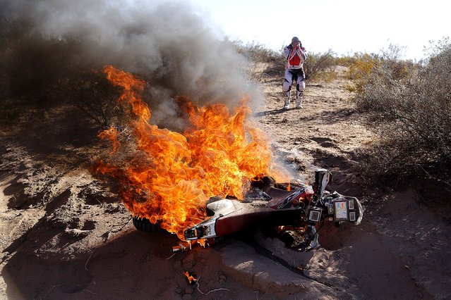 Honda rider Paulo Goncalves of Portugal reacts as he sees his motorcycle burn during the fifth stage of the Dakar Rally between the cities of Chilecito and Tucuman in San Miguel de Tucuman, Argentina, on January 9, 2014. (Photo by Victor R. Caivano/Associated Press)