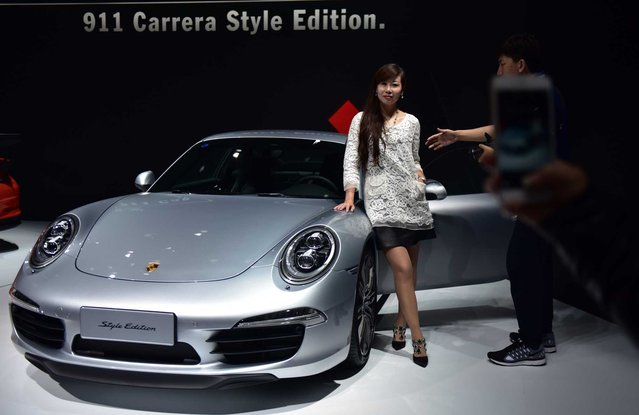 A woman poses next to a Porsche 911 Carrera Style Edition at the 16th Shanghai International Automobile Industry Exhibition in Shanghai on April 20, 2015. Global car makers showed off hundreds of vehicles in China's commercial hub Shanghai on April 20, as the world's biggest auto market continues to attract despite a sharp deceleration in sales growth. (Photo by Johannes Eisele/Getty Images)