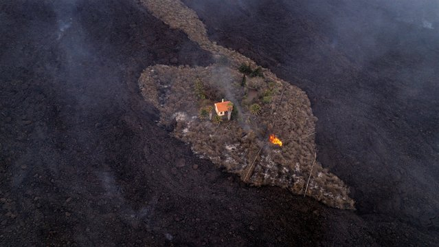 In this photo provided by iLoveTheWorld, a house remains intact as lava flows after a volcano erupted near Las Manchas on the island of La Palma in the Canaries, Spain, Monday, September 20, 2021. A dormant volcano on a small Spanish island in the Atlantic Ocean erupted on Sunday, forcing the evacuation of thousands of people. Huge plumes of black-and-white smoke shot out from a volcanic ridge where scientists had been monitoring the accumulation of molten lava below the surface. (Photo by Alfonso Escalero/iLoveTheWorld via AP Photo)