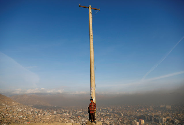 An Afghan boy stands in the sun on a hilltop overlooking Kabul, Afghanistan November 19, 2018. (Photo by Mohammad Ismail/Reuters)