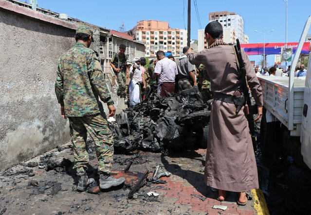 Security personnel a vehiclestand amid the wreckage of a vehicle at the site of a deadly car bomb attack that targeted two senior government officials, who survived, security officials said, in the port city of Aden, Yemen, Sunday, October 10, 2021. Aden has been the seat of the internationally recognized government of President Abed Rabbo Mansour Hadi since the Iranian-backed Houthi rebels took over the capital, Sanaa, triggering Yemen's civil war. (Photo by Wael Qubady/AP Photo)