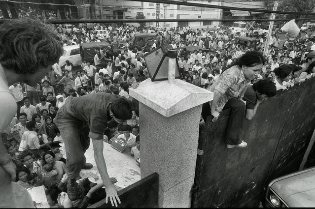 In this April 29, 1975 file photo, South Vietnamese civilians scale the 14-foot wall of the U.S. embassy in Saigon, trying to reach evacuation helicopters as the last Americans depart from Vietnam. (Photo by AP Photo)