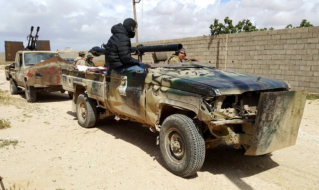 Members of forces loyal to Libya's eastern government sit in armed vehicles during clashes with the Shura Council of Libyan Revolutionaries, an alliance of former anti-Gaddafi rebels who have joined forces with Islamist group Ansar al-Sharia, in Benghazi, Libya March 14, 2016. (Photo by Reuters/Stringer)