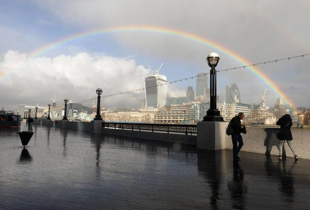 People walk along the Southbank as a rainbow appears over the city of London, on February 4, 2014. (Photo by Nick Ansell/PA Wire)