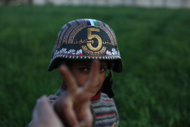 "A picture made available on 18 March 2016 shows a Syrian boy wearing the helmet drawn on by Akram Abo al-Foz, Hamorieh, outskirts of Damascus, Syria, 16 March 2016. Akram Abo al-Foz, a Syrian artist, celebrated the fifth anniversary of the Syrian revolution against Bashar Assad's regime by painting the arabic words ""Five years and we are still going on"" on an army safety helmet. al-Foz says ""I want the men of my community to wear it in their daily life as a symbolic message that we will keep on living our life without fear"". (Photo by Mohammed Badra/EPA)"