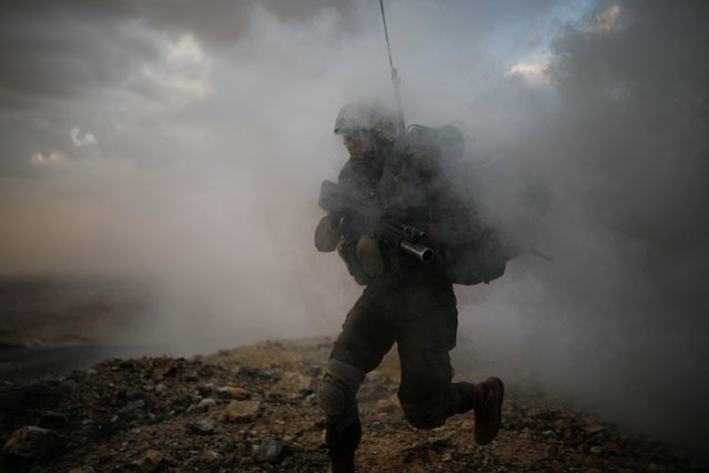 An Israeli soldier from the Nahal Infantry Brigade runs through smoke released from a smoke grenade during an urban warfare drill near an abandoned hotel in Arad, southern Israel February 8, 2017. (Photo by Amir Cohen/Reuters)
