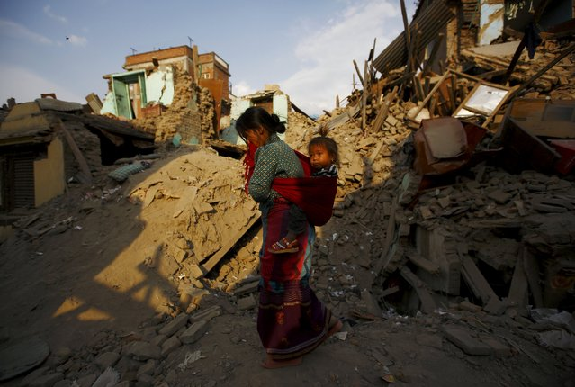 A woman carrying a girl walks along collapsed houses after the April 25 earthquake at Sankhu, on the outskirts of Kathmandu May 6, 2015. (Photo by Navesh Chitrakar/Reuters)