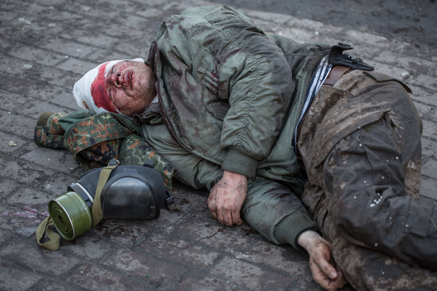 An injured anti-government protester lies on the ground during clashes with riot police outside Ukraine's parliament on February 18, 2014 in Kiev, Ukraine. (Photo by Vladislav Sodel/Kommersant Photo via Getty Images)