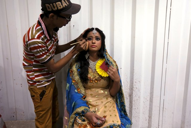 A model has her makeup applied backstage during a self grooming bridal beauty workshop at a local mall in Karachi, Pakistan, March 22, 2016. (Photo by Akhtar Soomro/Reuters)