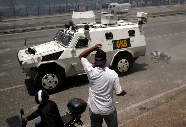 """An opposition demonstrator is struck by a Venezuelan National Guard vehicle on a street near the Generalisimo Francisco de Miranda Airbase """"La Carlota"""", in Caracas, Venezuela April 30, 2019. (Photo by Ueslei Marcelino/Reuters)"""