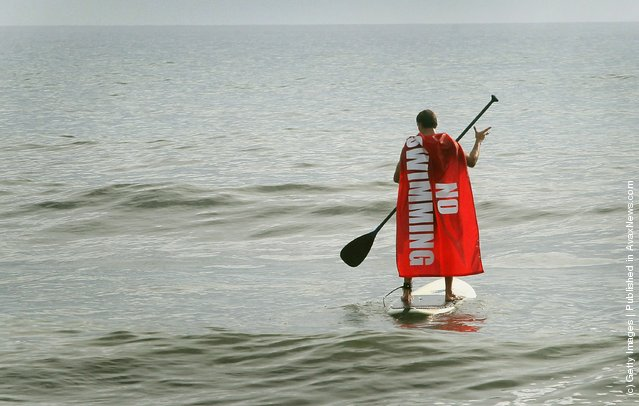 A surfer paddles out to catch a wave as the surf begins to pick up in front of Hurricane Irene