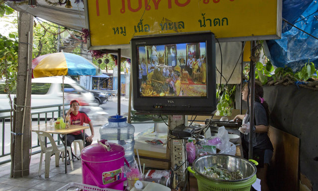 Television at a street noodles shop broadcast Thailand's King Maha Vajiralongkorn's coronation ceremony Saturday, May 4, 2019, in Bangkok, Thailand. Saturday began three days of elaborate centuries-old ceremonies for the formal coronation of Vajiralongkorn, who has been on the throne for more than two years following the death of his father, King Bhumibol Adulyadej, who died in October 2016 after seven decades on the throne. (Photo by Gemunu Amarasinghe/AP Photo)