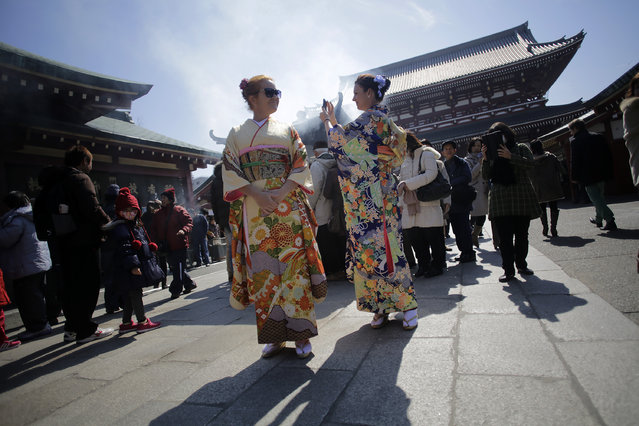 Foreign tourists wearing traditional Japanese kimonos visit Asaskusa Sensoji temple in Tokyo, Tuesday, March 4, 2014. Asakusa is an old town in Tokyo that draws many tourists from across the world. (Photo by Eugene Hoshiko/AP Photo)