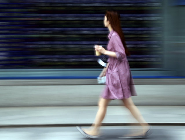 A woman walks by an electronic stock board of a securities firm in Tokyo, Friday, May 15, 2015. Shares in Asia were uneven on Friday as the big markets in Japan and Hong Kong got a lift from the rebound on Wall Street, but weak data dragged Chinese shares lower. (Photo by Koji Sasahara/AP Photo)