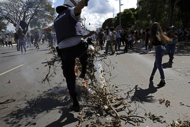 A policeman stomps on a barricade set on fire by demonstrators taking part in a nation-wide education strike, in Brasilia, Brazil, Wednesday, May 15, 2019. Federal education officials this month announced budget cuts of $1.85 billion for public education, part of a wider government effort to slash spending. (Photo by Eraldo Peres/AP Photo)