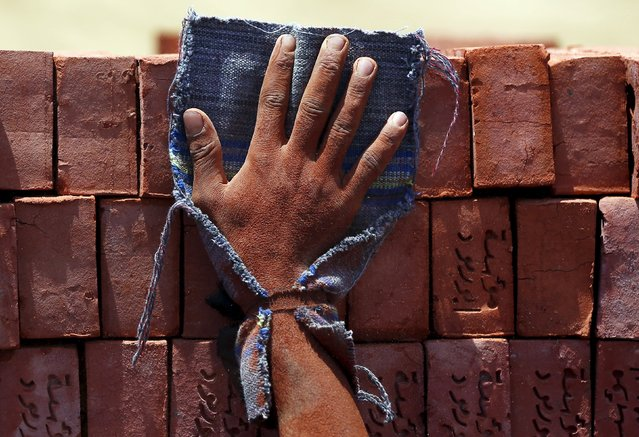 A hand of a labourer pushes bricks at a traditional brick factory in Arab Mesad district of Helwan, northeast of Cairo, May 14, 2015. (Photo by Amr Abdallah Dalsh/Reuters)