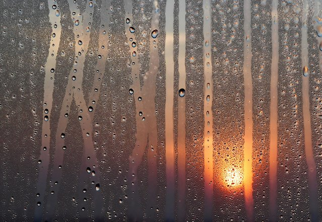 The sun rises behind a window streaked with condensation at Reagan National Airport in Arlington, Va. on August 30, 2018. (Photo by Matt McClain/The Washington Post)