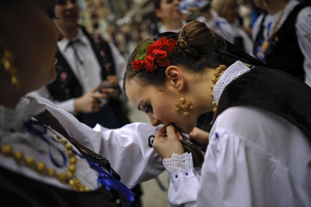 A regional dancer prepares to take part in a dance, in Plaza del Castillo square,  in Pamplona, northern Spain, Saturday, May 23, 2015. (Photo by Alvaro Barrientos/AP Photo)