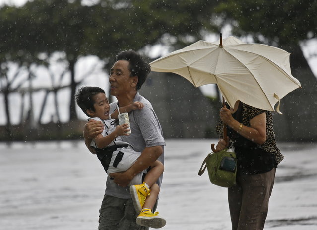 A family from Mainland China battle against strong wind near the waterfront in Hong Kong Wednesday, August 14, 2013. (Photo by Vincent Yu/AP Photo)