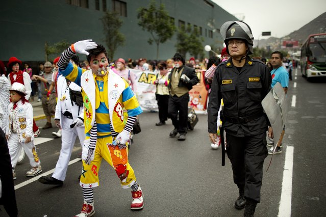 A clown greets photographers during a march commemorating the Peruvian clown day in Lima Peru, Monday, May 25, 2015. (Photo by Rodrigo Abd/AP Photo)