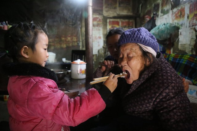 5-year-old Chinese girl Wang Anna feeds her great-grandmother at home in Zhuyuan village, Guizhou province, China on March 3, 2017. Chinese girl called Wang Anna, 5, takes care of her ill grandmother and 92-year-old great-grandmother on her own every day in a mountainous village in Zhima town, Zunyi city, southwest China's Guizhou province. Her father went to jail before she was born and her mother remarried after gave birth to her. Although she is just five years old, she started to shoulder the responsibility to look after ill grandmother and elderly great-grandmother. (Photo by Imaginechina/Rex Features/Shutterstock)