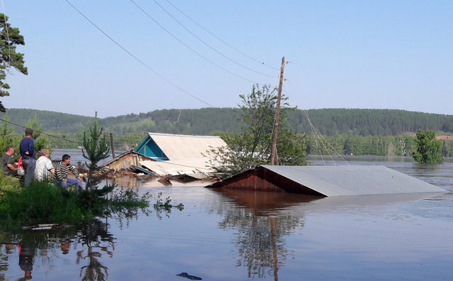 Houses in a flooded street in Irkutsk Region, Russia on June 29, 2019. Heavy rains have caused floods in Russia's Irkutsk Region; a state of emergency has been declared in the area. (Photo by Anna Moskvitina/TASS )