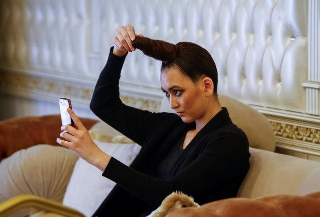 A model checks her hair backstage during Kazakhstan Fashion Week in Almaty, Kazakhstan, April 20, 2016. (Photo by Shamil Zhumatov/Reuters)