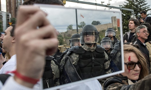 """A protester holds a mirror in front of the cordon of the riot police who blocked the street for the Constitutional Court, during the protest dubbed """"Colorful Revolution"""" against Macedonian President Ivanov's decision on wiretapping amnesty, in Skopje, The Former Yogoslav Republic of Macedonia, 23 April 2016. Ivanov on 12 April decided to abolish all judicial cases related to the big wire-tapping scandal that brought the country to early general elections scheduled for 05 June. (Photo by Georgi Licovski/EPA)"""