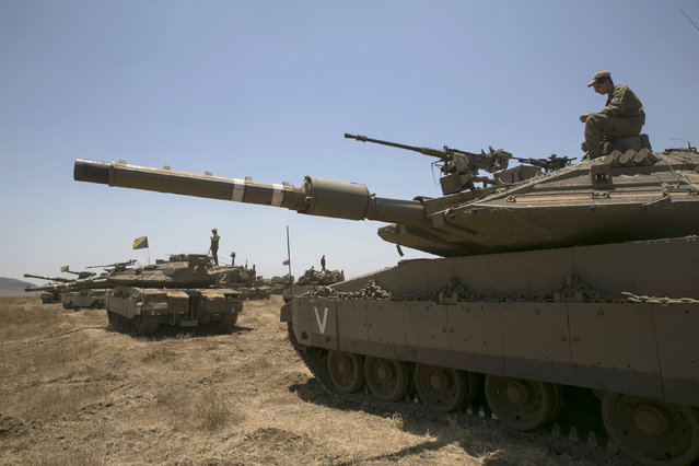 An Israeli soldier sits atop a tank during an exercise in the Israeli-occupied Golan Heights, near the ceasefire line between Israel and Syria June 17, 2015. Israel signaled readiness on Tuesday to intervene if Syrian refugees were to throng to its armistice line on the Golan Heights, after Israel's Druze Arab minority stepped up a public campaign to help brethren caught up in the civil war next door. REUTERS/Baz Ratner