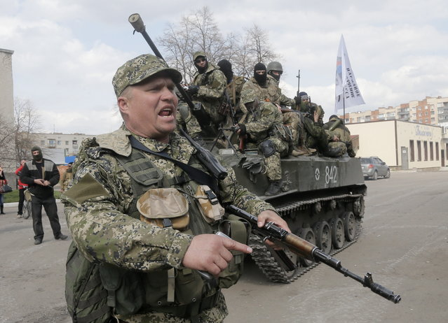 A pro-Russian gunman clears the way for a combat vehicle with gunmen on top in Slovyansk, Ukraine, Wednesday, April 16, 2014. The troops on those vehicles wore green camouflage uniforms, had automatic weapons and grenade launchers. At least one had the St. George ribbon attached to his uniform, which has become a symbol of the pro-Russian insurgency in eastern Ukraine. (Photo by Efrem Lukatsky/AP Photo)