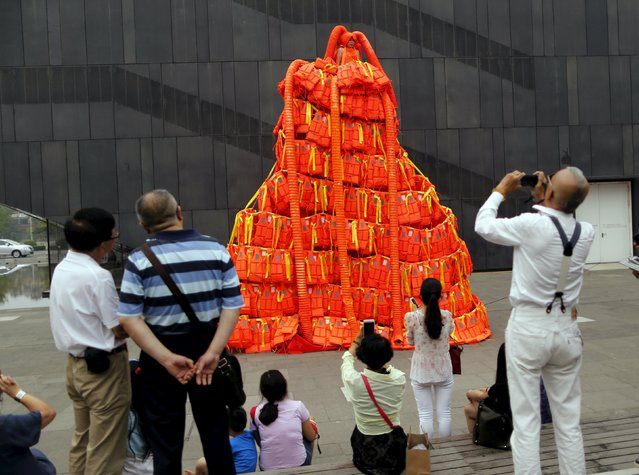 "People take pictures of a new artwork entitled ""Jumping Orange"" by artist Kong Ning, which consists of 443 life jackets, at a yard of an art gallery in Beijing, China, June 27, 2015. (Photo by Kim Kyung-Hoon/Reuters)"