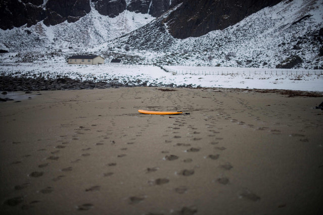 A surfboard is left on the sandy beach at Unstad along the northern Atlantic Ocean on March 12, 2017, where the water temperatures is at five degrees centigrade and the air temperature is at minus two degrees centigrade. (Photo by Olivier Morin/AFP Photo)