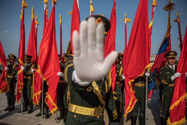 A member of an honor guard gestures to the photographer to stop taking photos prior to a welcome ceremony for Colombian President Ivan Duque Marquez at the Great Hall of the People in Beijing, China, 31 July 2019. Colombian President Ivan Duque Marquez is on a state visit to China from 28 July to 31 July 2019. (Photo by Roman Pilipey/EPA/EFE)