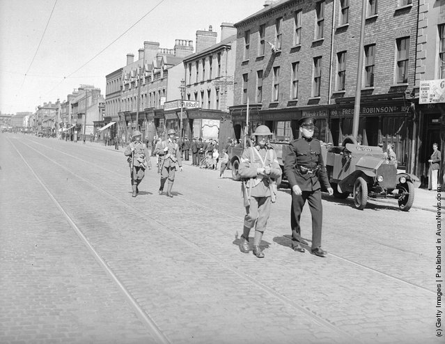 1935:  Police and military patrolling York street, Belfast, clear of traffic after recent rioting. An armoured car ia parked at the kerb