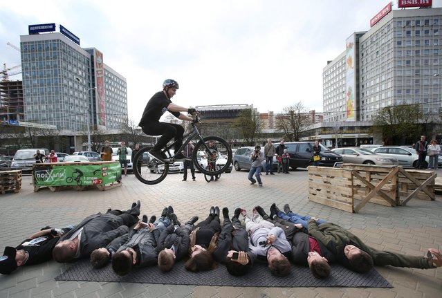 "A member of the bicycling team ""Minsk-trial"" jumps over lying volunteers showing his skills in Minsk, Belarus, 18 April 2014. The show runs during the ""Motoveloexpo"" exhibition in Minsk. (Photo by Tatyana Zenkovich/EPA)"