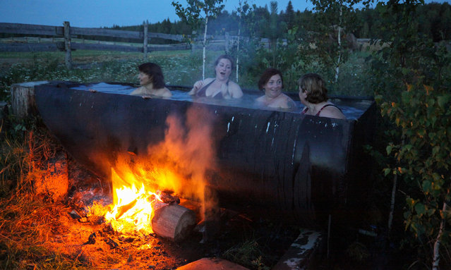 "Latvian women bath in a huge tub heated by a bonfire in the village of Bobrovka, some 350 km of Omsk, on July 31, 2019. The people of the remote Siberian village Bobrovka call it the ""Little Latvia of the Taiga"", where Baltic traditions continue more than 100 years after settlers from the region first arrived. (Photo by Alexei Malgavko/AFP Photo)"