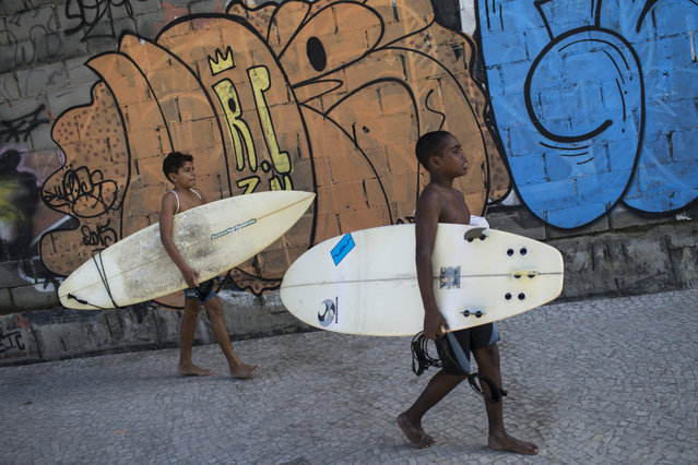 """In this  May 21, 2015 photo, Wesley Mario, right, and Loran de Almeida, both 13, walk back to Rocinha slum after surfing at Sao Conrado beach in Rio de Janeiro, Brazil. """"We bring children who have nothing to do to the beach, it's the most democratic place there is, where they can feel at ease"""", says Ricadro Ramos, who created the Rocinha Surf School two decades ago. """"They don't even need to pay anything to be here"""". (Photo by Felipe Dana/AP Photo)"""