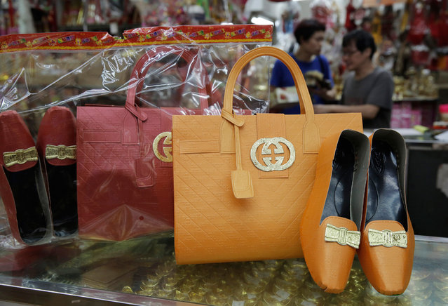 Paper offerings featuring a pair of shoes and a hand bag are displayed at a store in Hong Kong, Friday, May 6, 2016. Gucci and its parent company apologized Friday after drawing heavy criticism for a warning to some Hong Kong shops not to sell paper offerings for the deceased resembling the fashion brand's luxury products. (Photo by Kin Cheung/AP Photo)