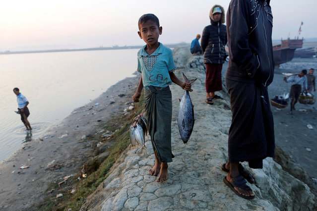 A Rohingya boy carries fishes at the beach in Sittwe in the state of Rakhine, Myanmar March 2, 2017. (Photo by Soe Zeya Tun/Reuters)