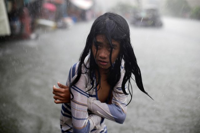 A Filipino girl tries to keep herself warm as she wades in floodwaters in the coastal village of Malabon, north of Manila, Philippines on Wednesday, July 8, 2015. (Photo by Aaron Favila/AP Photo)