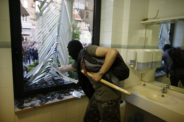A pro-Russia protester breaks a window at the governor's business premises in Donetsk, eastern Ukraine May 3, 2014. (Photo by Marko Djurica/Reuters)