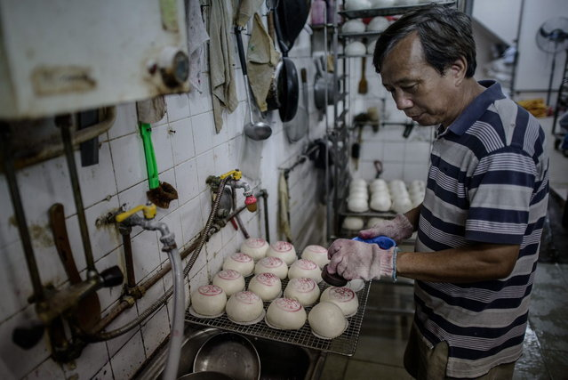 "A man stamps traditional buns with the Chinese character ""Peace"" in a bakery during the ""Bun Festival"" on the island of Cheung Chau in Hong Kong on May 6, 2014. The traditional ""Bun Festival"" is held every year to placate the hungry ghosts of old pirates. Legend has it that buns bring good luck to the island's fisherman protecting them from the spirits of pirates that once lurked in the region. (Photo by Philippe Lopez/AFP Photo)"