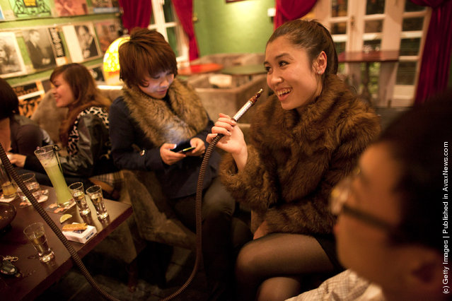 Trang Anh (R) smokes a shisha water pipe with Chinh at a local trendy bar