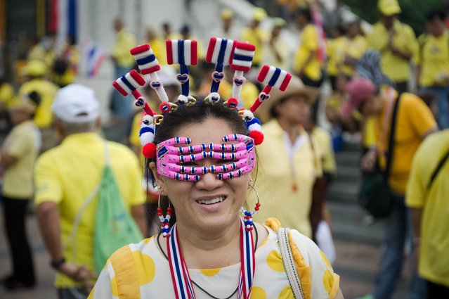 An anti-government protester goes a march to mark the 64th anniversary of the coronation of Thai King Bhumibol Adulyadej in Bangkok on May 5, 2014. Thailand's revered King Bhumibol Adulyadej made a rare public appearance on May 5 to mark the 64th anniversary of his coronation, as the political turmoil gripping his kingdom enters a critical phase. (Photo by Nicolas Asfouri/AFP Photo)