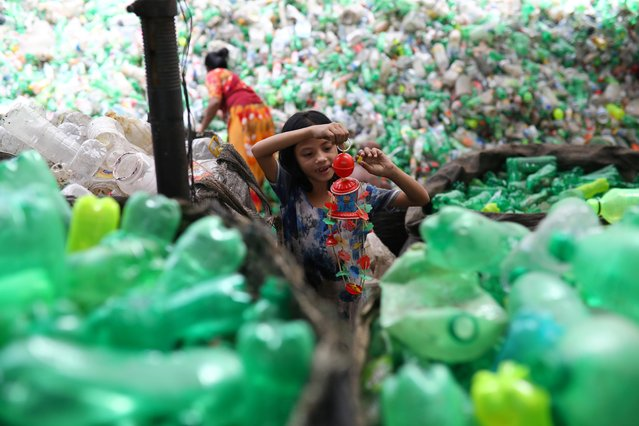 A girl plays with a toy found in a plastic recycling factory in Dhaka, Bangladesh, July 8, 2019. (Photo by Mohammad Ponir Hossain/Reuters)
