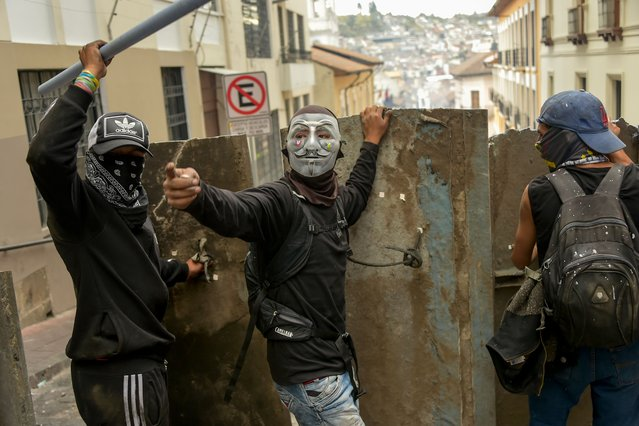 Demonstrators protect themselves with makeshift shields during clashes with riot police in Quito, as thousands march against Ecuadorean President Lenin Moreno's decision to slash fuel subsidies, on October 9, 2019. (Photo by Rodrigo Buendia/AFP Photo)