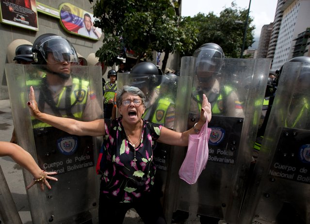 A demonstrator is blocked by Bolivarian National police during an anti-government march to the headquarters of the national electoral body, CNE, in Caracas, Venezuela, Wednesday, May 18, 2016. Opposition protesters were blocked from reaching the CNE as they demand the government allow it to pursue a recall referendum against Venezuela's President Nicolas Maduro. (Photo by Fernando Llano/AP Photo)