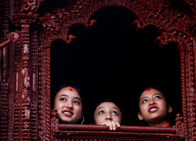 Former Living Goddess Kumari Matina Shakya looks through the window of a Kumari House during the Indra Jatra Festival in Kathmandu, Nepal September 13, 2019. The annual festival, named after Indra, the god of rain and heaven, is celebrated by worshipping, rejoicing, singing, dancing and feasting in Kathmandu Valley to mark the end of monsoon season. Indra, the living goddess Kumari and other deities are worshipped during the festival. (Photo by Navesh Chitrakar/Reuters)