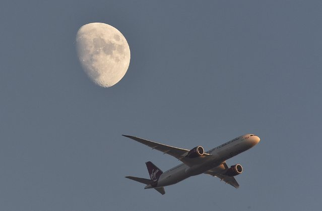 A Virgin Atlantic passenger plane flies in the sky with the moon seen in the background, in London, Britain January 19, 2016. (Photo by Toby Melville/Reuters)