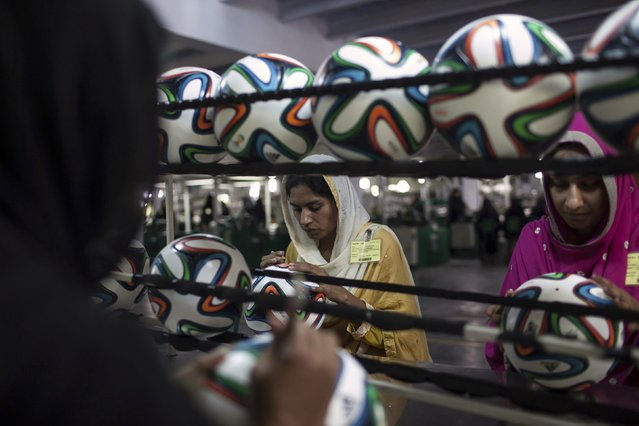 An employee conducts a final check to fix any cavity in the seams of a ball inside the soccer ball factory that produces official match balls for the 2014 World Cup in Brazil, in Sialkot, Punjab province May 16, 2014. (Photo by Sara Farid/Reuters)